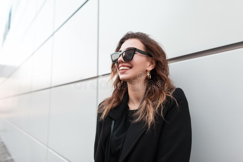 Pretty hipster young woman in black elegant stylish coat in sunglasses is smiling standing near a gray modern wall in the city. royalty free stock photo