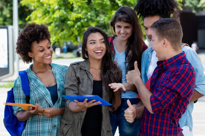 Pretty hispanic female student learning with group of latin and african american young adults. Outdoor at campus of university stock photos