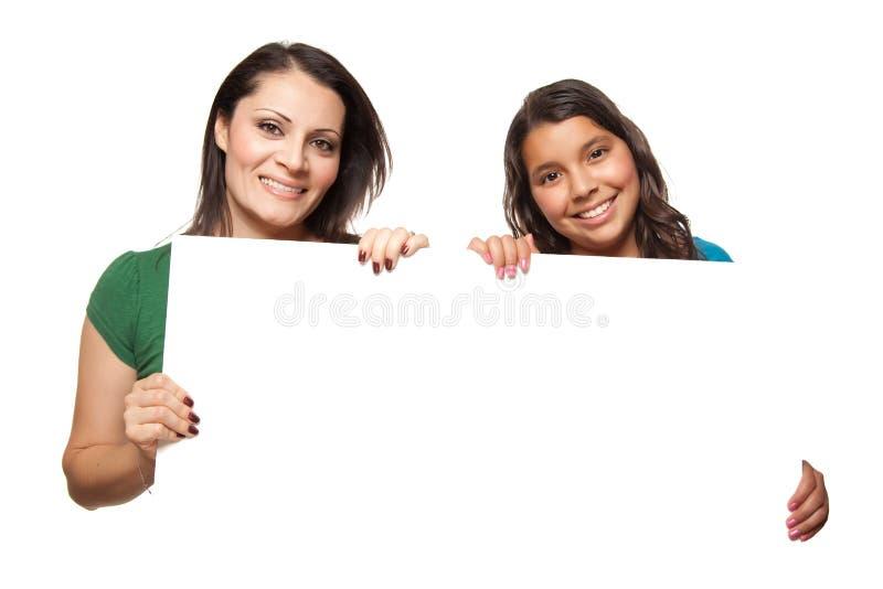 Pretty Hispanic Girl & Mother Holding Board royalty free stock photos