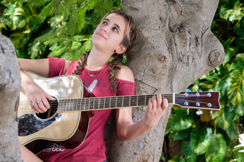 Pretty hispanic teenage girl playing an acoustic guitar sitting. On a tree branch royalty free stock photography