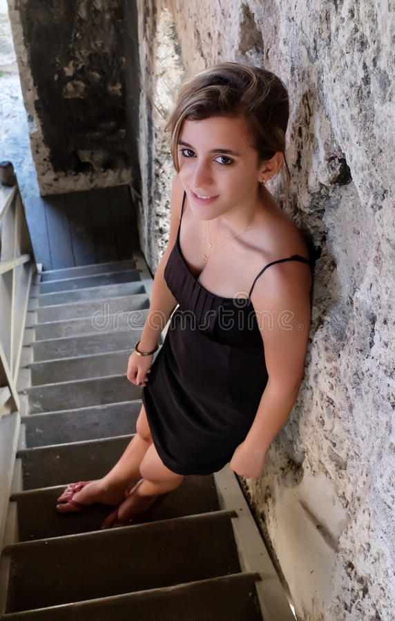 Pretty hispanic teenage girl standing on an old wooden staircase. Beautiful hispanic teenage girl standing on an old wooden staircase royalty free stock images