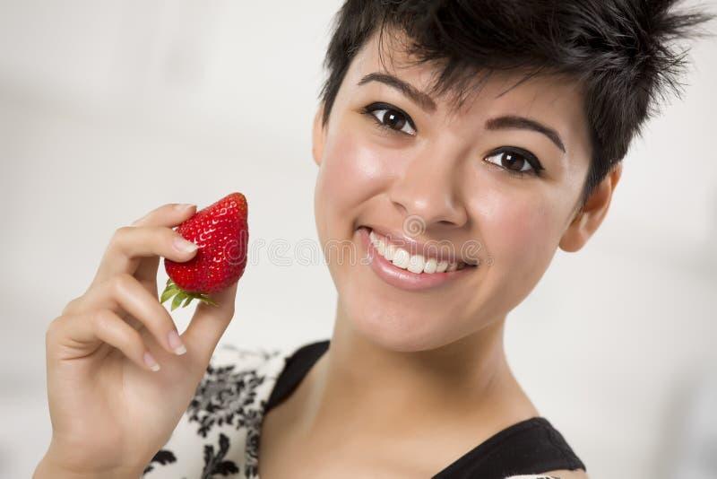 Pretty Hispanic Woman Holding Strawberry Stock Photography