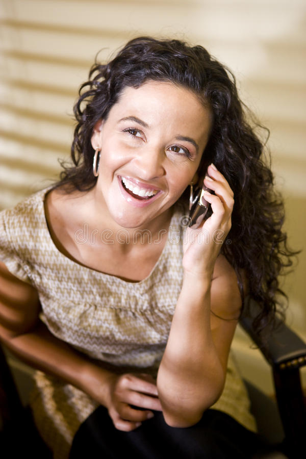Pretty Hispanic woman talking on a mobile phone stock images