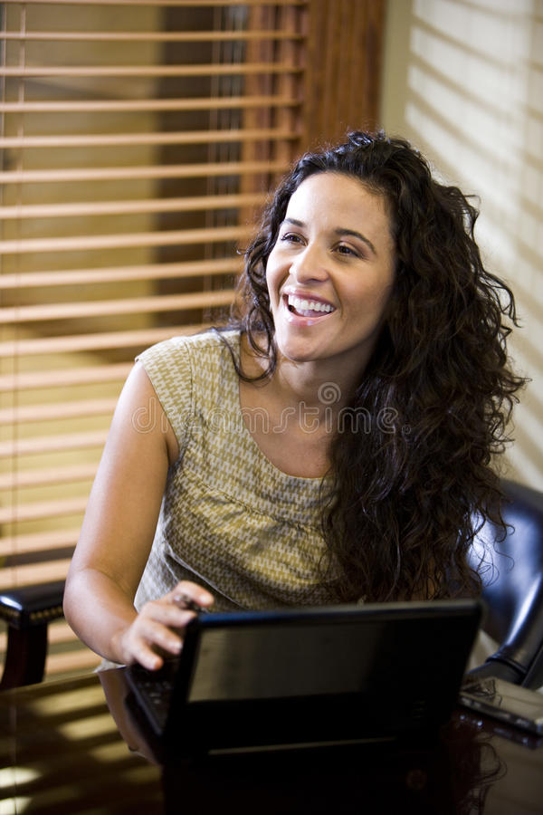 Pretty Hispanic woman using laptop computer stock photo
