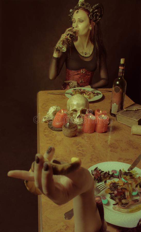Dinner with Satan. Pretty horned gothic lady drinking wine during a dinner stock photos