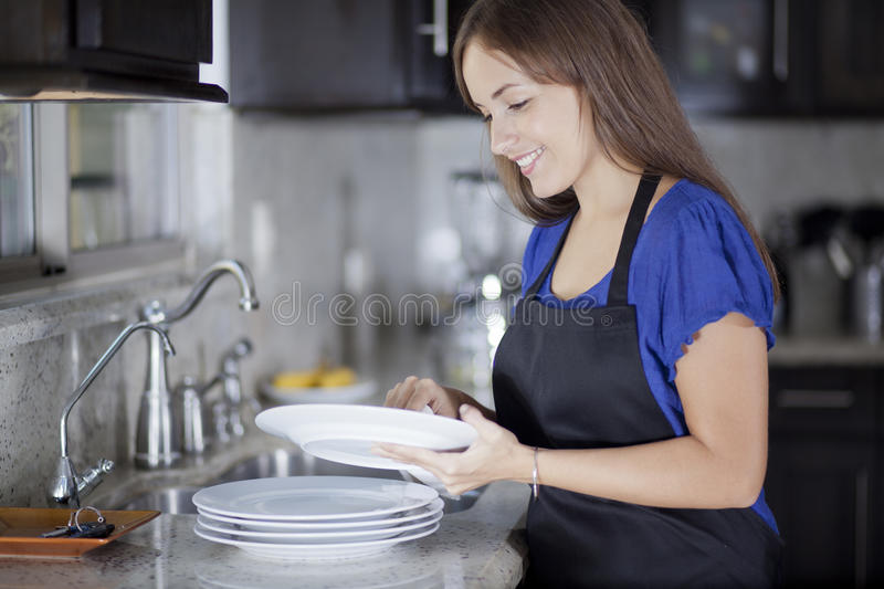 Pretty housewife doing some chores. Cute young housewife washing the dishes in the kitchen stock photography