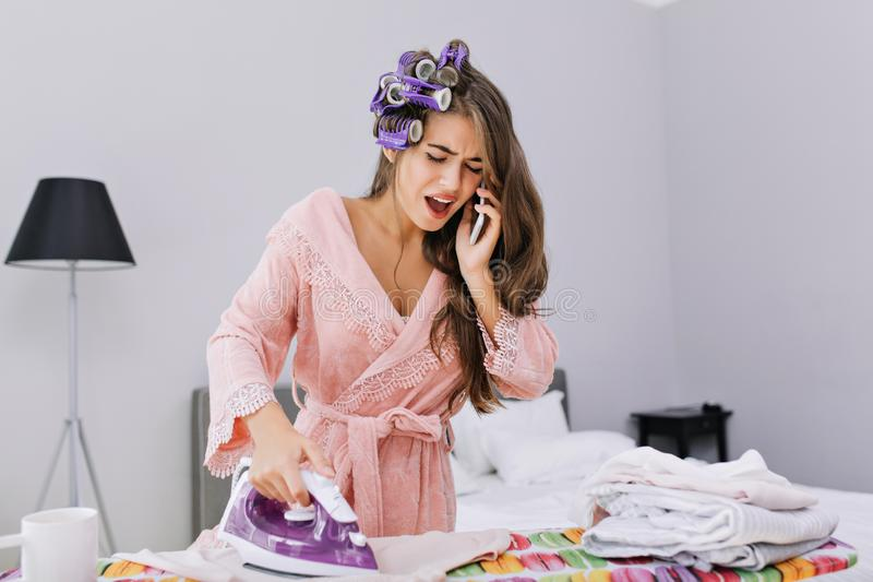 Pretty housewife in pink bathrobe and curler ironing clothes and speaking on phone. She looks astonished and busy. Pretty housewife in pink bathrobe and curler stock images