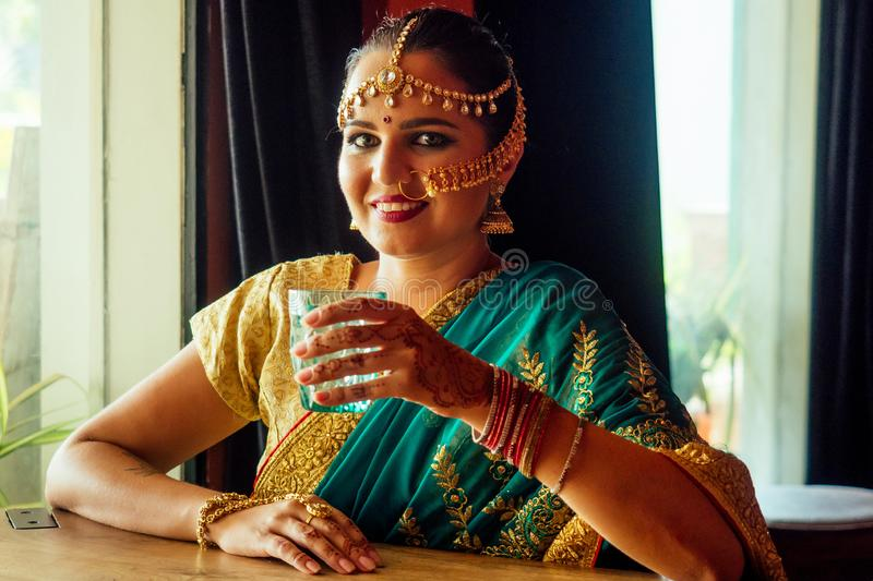 Pretty Indian Asian girl in sari holding glass of plain water, sitting at home kitchen near window royalty free stock images