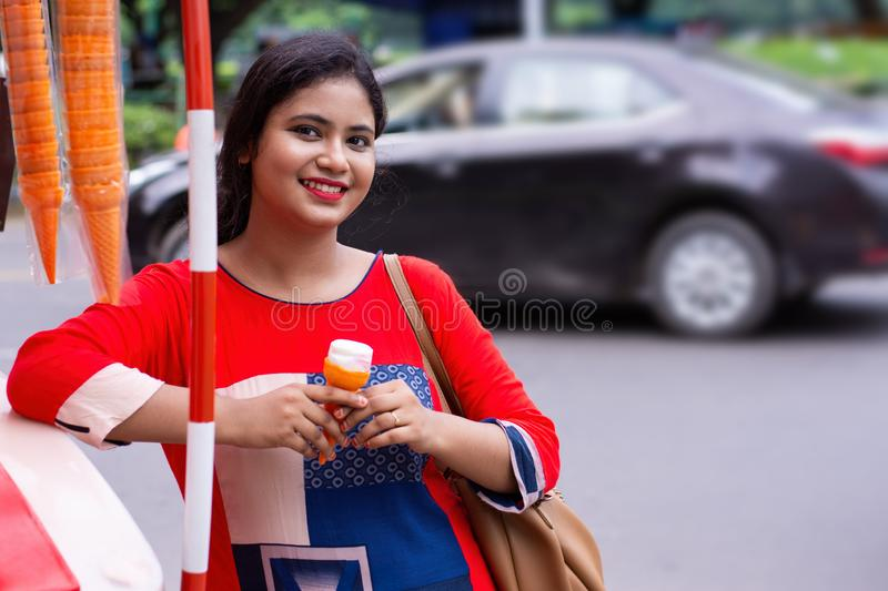 Pretty Indian/Asian young girl eating Ice Cream in cone, standing near taxi or ice cream shop. Happy smile face of Indian woman stock photo