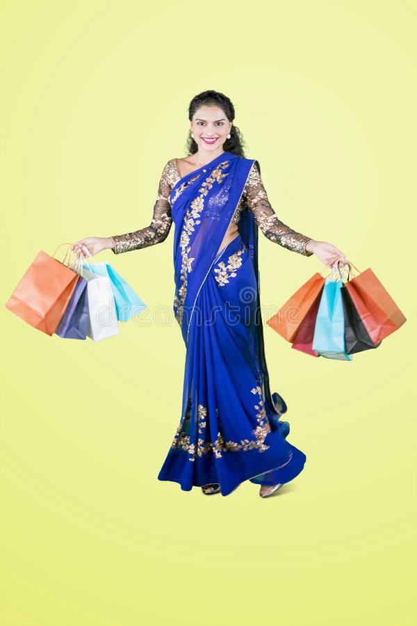 Pretty Indian girl carries shopping bags on studio stock image