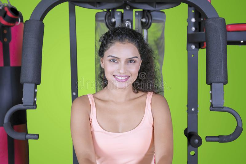 Pretty Indian woman sits on a fitness machine stock photo
