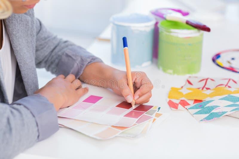 Pretty interior designer drawing on colour samples stock photo