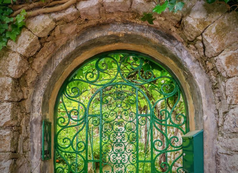 Pretty iron gate leading to a green summer garden. stock image