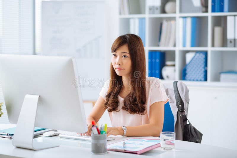 Pretty Japanese manager. Young pretty Japanese manager working on computer stock photography