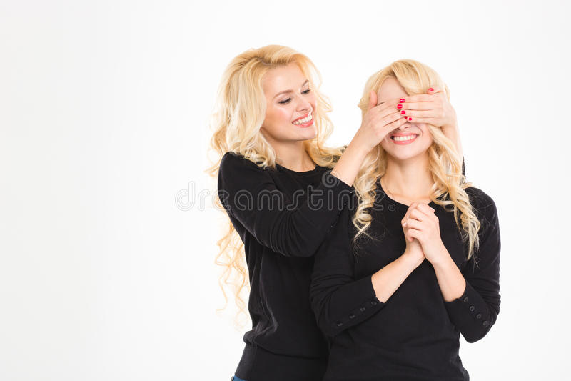 Pretty joyful blonde sister twin covered eyes to another isolated royalty free stock photography