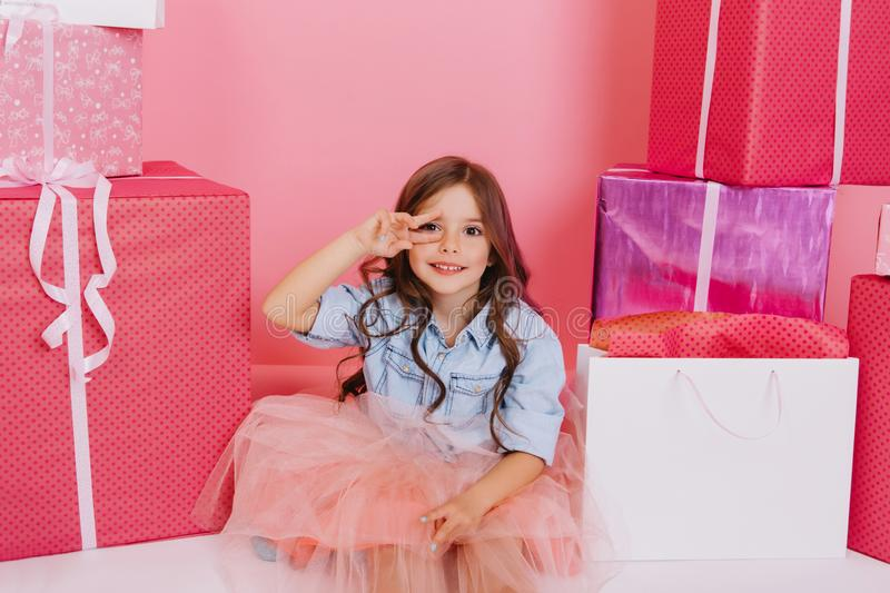 Pretty joyful young girl in tulle skirt sitting suround colorful giftboxes on pink background. Lovely sweet moments of. Little princess, pretty friendly child stock photos
