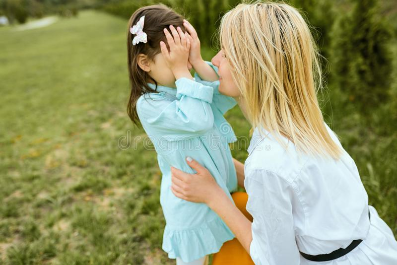 Pretty kid playing hide-and-seek with young mother outdoor. Portrait of joyful woman and her cute child playing in the park. royalty free stock photos