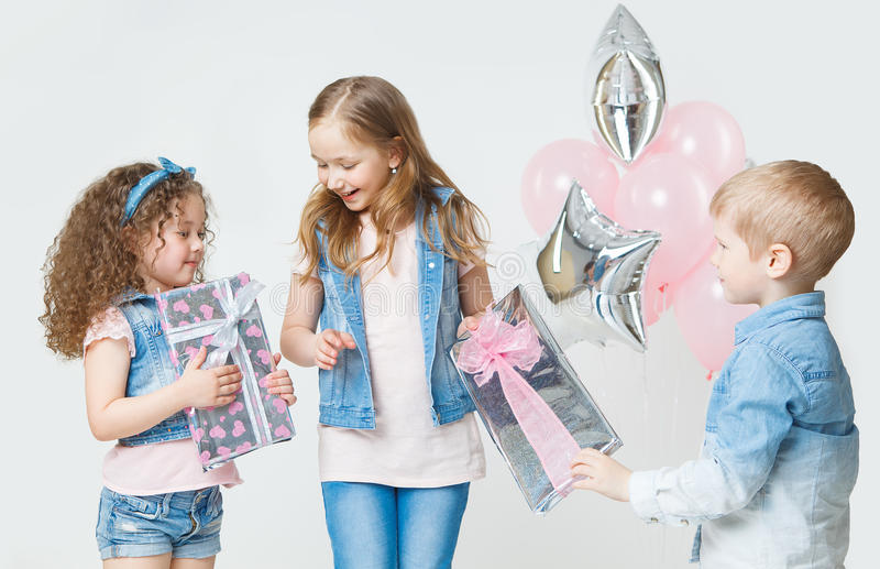Pretty kids on birthday party giving presents in jeans clothes. Balloons. Smiling stock image