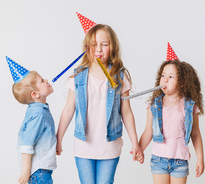 Pretty kids on birthday party having fun in jeans clothes and festive cap. Studio royalty free stock images