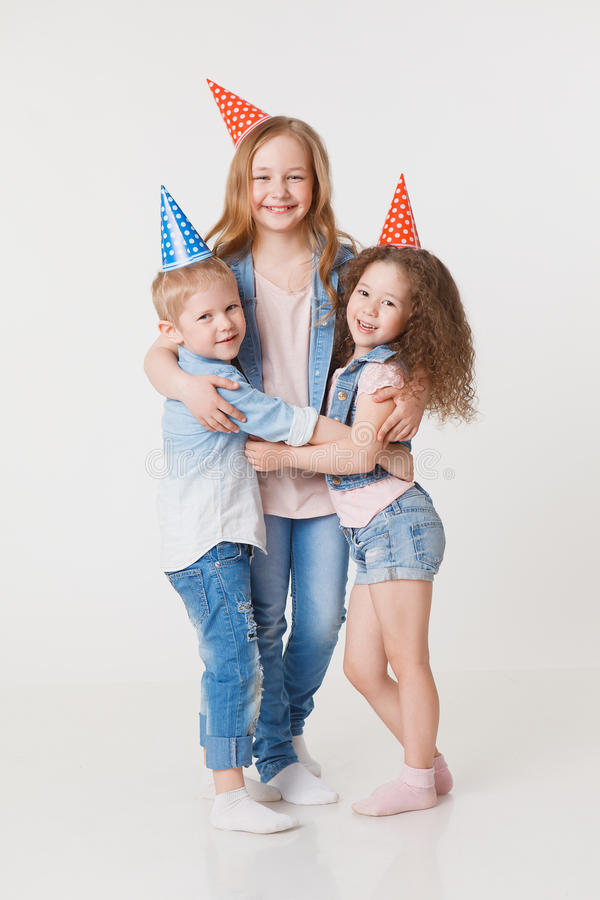 Pretty kids hug and congratulate in jeans clothes and festive caps. Funny. Studio royalty free stock images