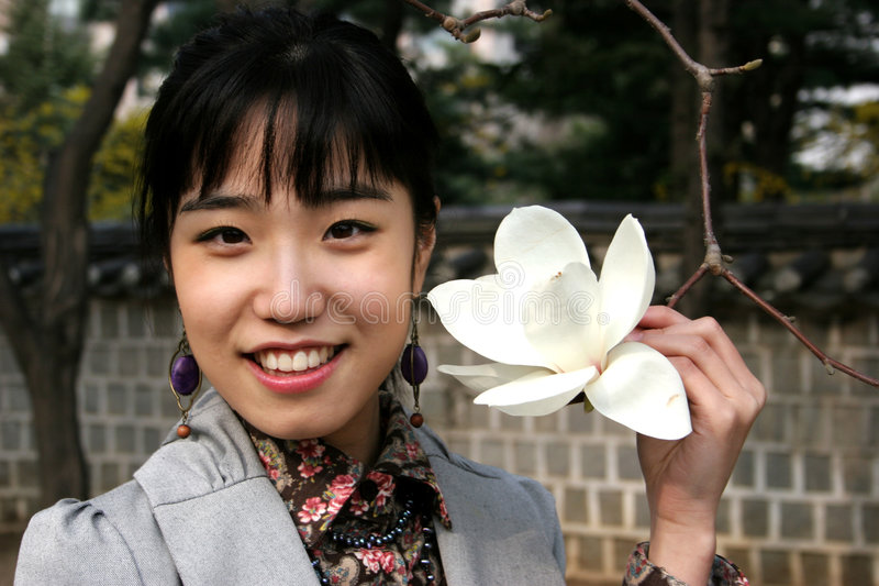 Pretty Korean woman holding a flower stock images