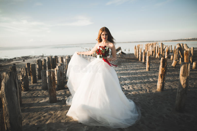 Pretty lady, bride posing in a wedding dress near sea on sunset.  royalty free stock images
