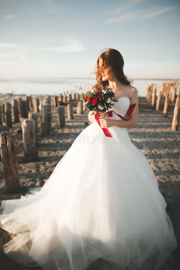 Pretty lady, bride posing in a wedding dress near sea on sunset.  stock photography