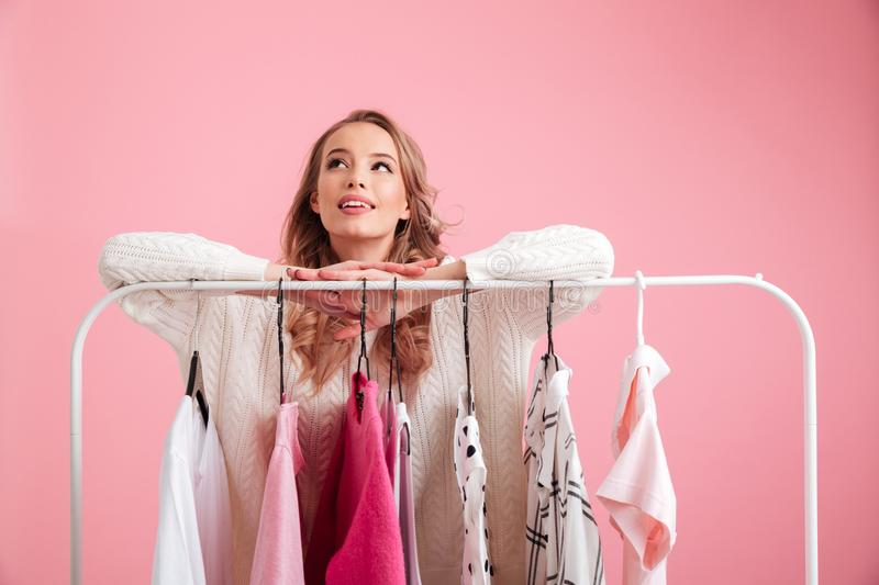 Pretty lady choosing clothes hanging on rack in workshop. stock image