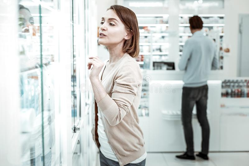 A pretty lady choosing the vitamins with her boyfriend at the background. A lady in a drugstore. A pretty short-haired lady choosing the vitamins with her royalty free stock image