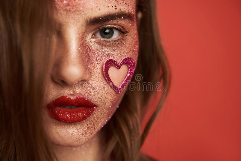 Pretty lady with creative make up and heart-shaped sticker on face stock image