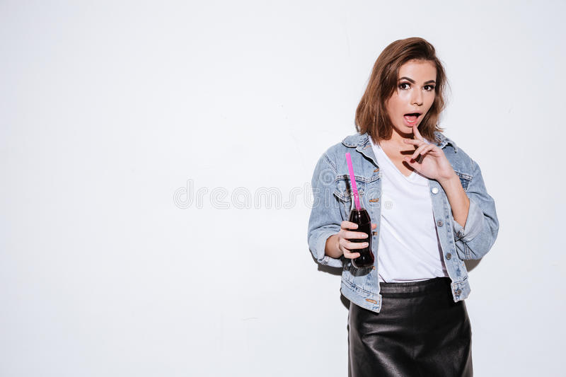 Pretty lady drinking aerated sweet water. Image of a young pretty lady dressed in jeans jacket standing over white background while drinking aerated sweet water royalty free stock image