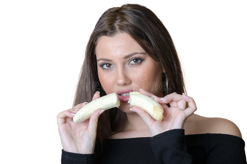 Pretty lady holding and split a banana. Cute brunette lady wear black shirt, holding and split a banana front of her face. Beautiful big lips, french nails and royalty free stock photo