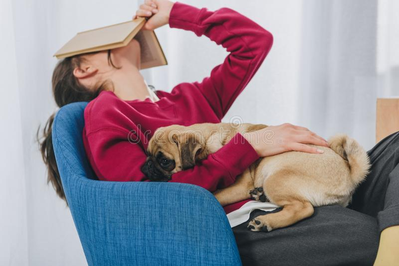 Pretty lady hugging pug and covering her face stock photo