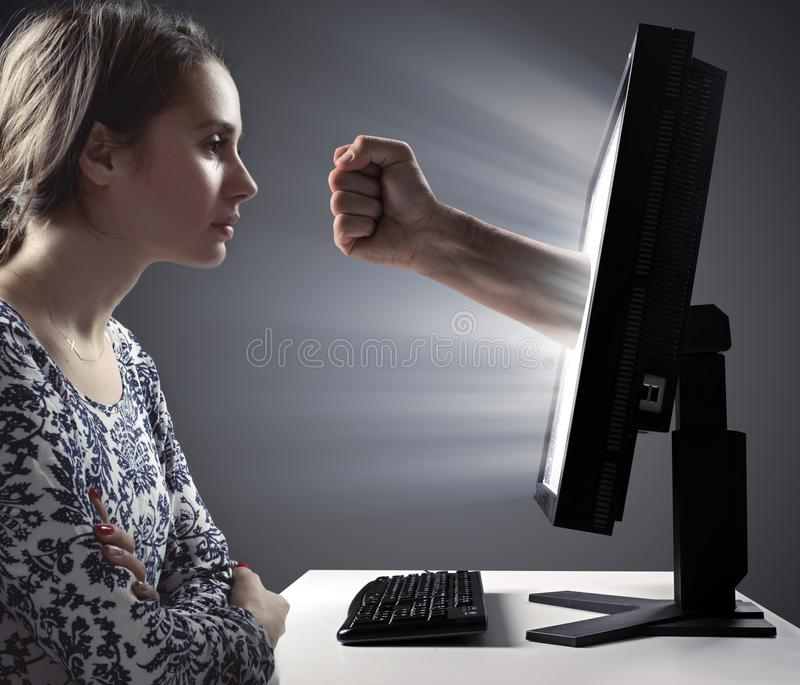 Pretty lady looking at the monitor - Internet violence symbol stock photo