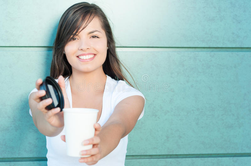 Pretty lady smiling offering fresh coffee. Pretty young lady smiling offering fresh coffee from takeaway mug outside on green wall with copy text area royalty free stock photos