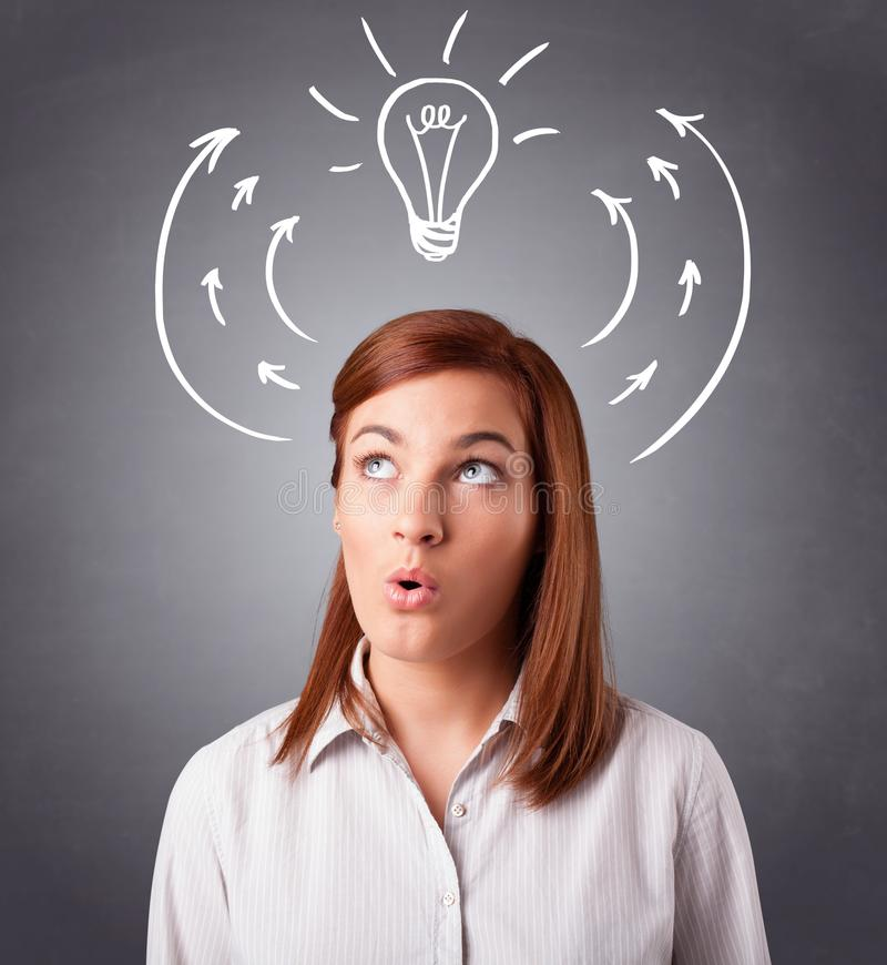 Pretty lady thinking with arrows and light bulb overhead. Pretty young lady standing and thinking with arrows and light bulb overhead royalty free stock photo