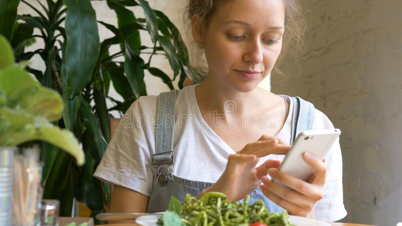 Pretty lady types on modern smartphone and eats green salad stock image