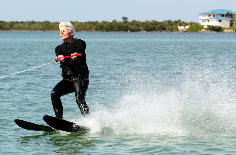 Pretty Lady Water Skiing. A pretty white haired older lady water skiing on a sunny day in front of a very nice home. Senior citizen wearing black wet suit. Copy stock photography