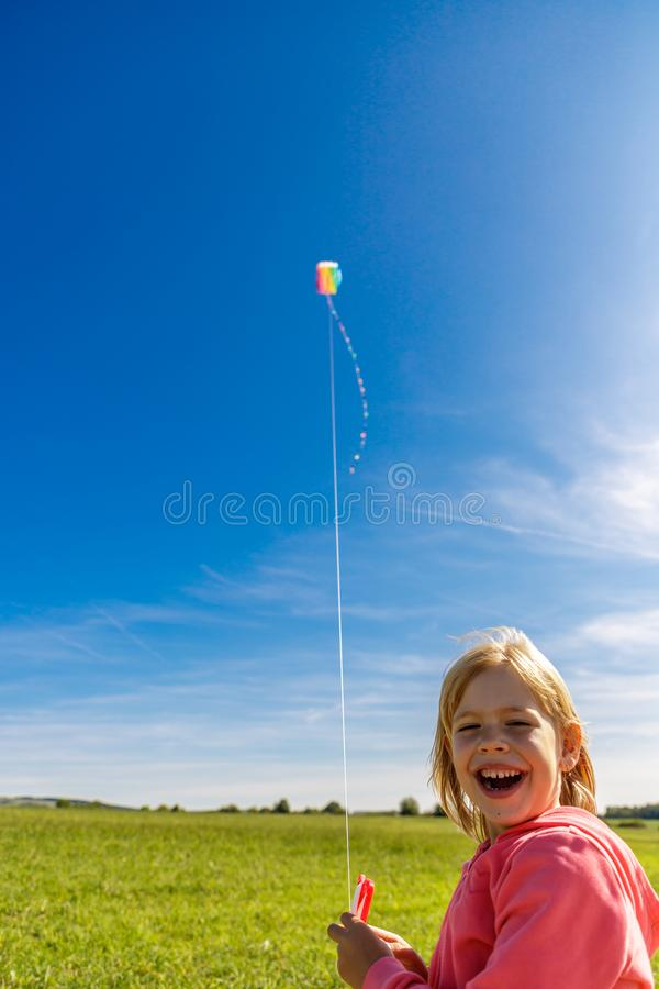 Pretty laughing little girl with blond hair on field in pink sweatshirt looks at colorful dragon in blue sky with soft clouds stock photos