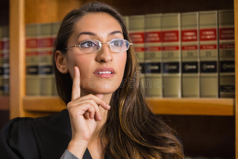 Pretty lawyer thinking in the law library royalty free stock images
