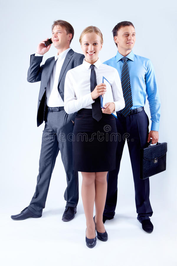 Pretty leader. Portrait of elegant businesswoman looking at camera with two colleagues behind royalty free stock photo
