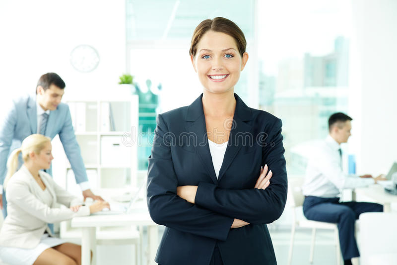 Pretty leader. A beautiful businesswoman looking at camera with working people on background royalty free stock photography