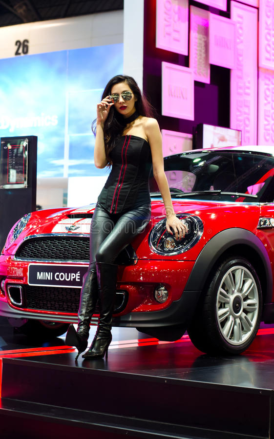 Pretty in leather jacket with a Mini coupe. stock photo
