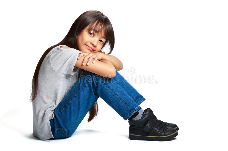 Pretty little asian girl sitting on the floor royalty free stock photography