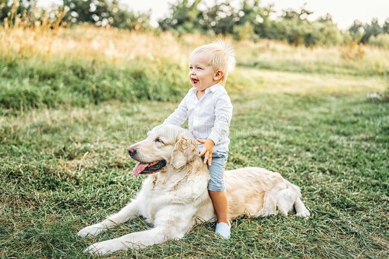 Pretty little baby boy have fun with dog. Cute little baby boy have fun with dog royalty free stock photography