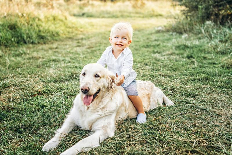 Pretty little baby boy have fun with dog. Cute little baby boy have fun with dog stock photography
