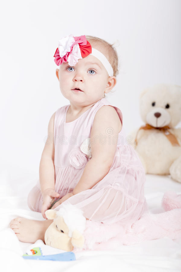 Pretty little baby girl in pink dress stock photos