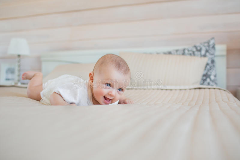 Pretty little baby tries of stand up on a bed royalty free stock photos