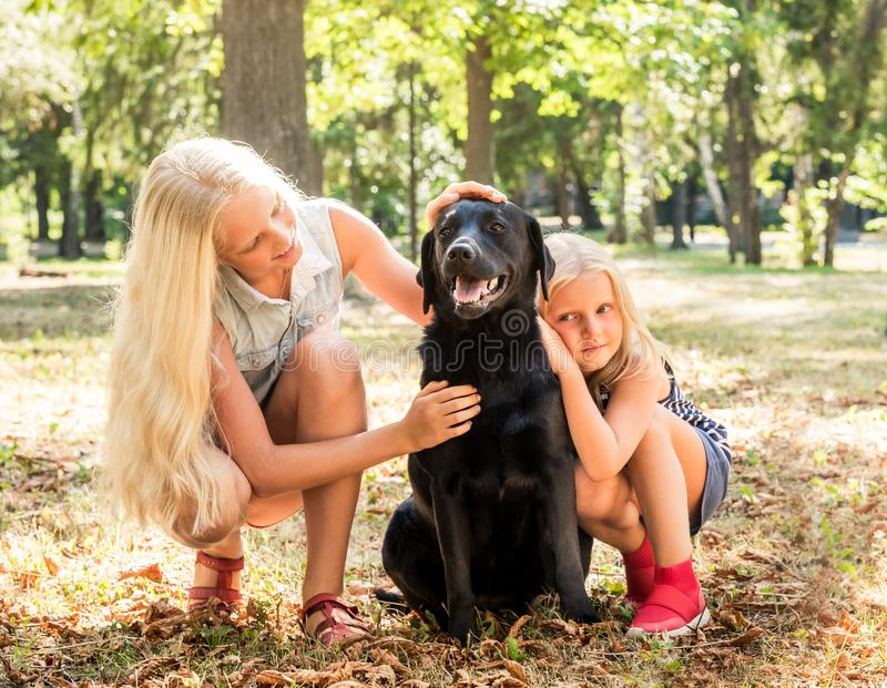 Little blond girls sit hugging a black dog in a park stock images