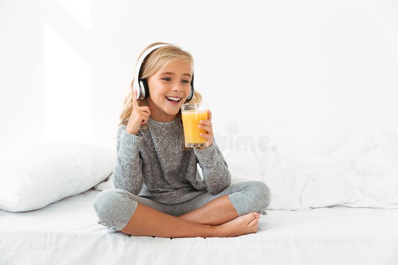 Pretty little blonde girl in gray pajamas holding glass of orange juice, while listening to music in bedroom stock photo